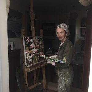 Artist standing in front of an easel dressed in paint-covered overalls
